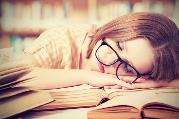 girl sleeping on top of pile of books