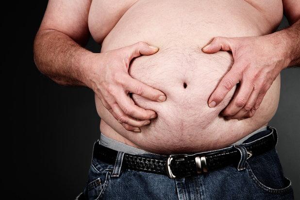 man clutching his beer belly