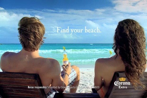 man and woman at the beach drinking Corona Extra