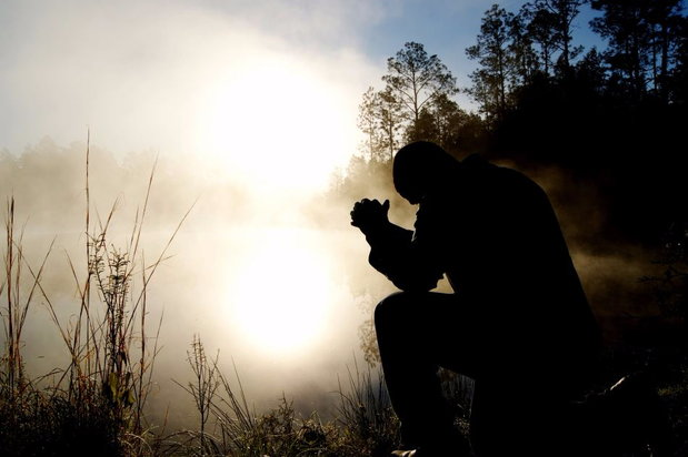 person praying outside in nature