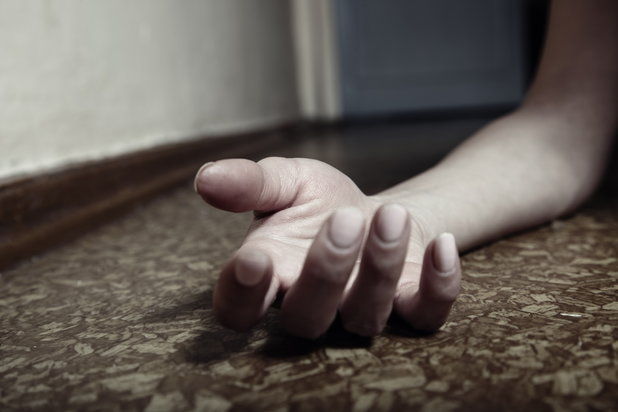 A hand lies on the floor after a drug addict overdoses on grey death.