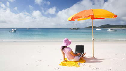 A woman working on her laptop at the beach.
