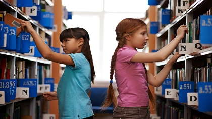 A pair of girls look for books in a library.