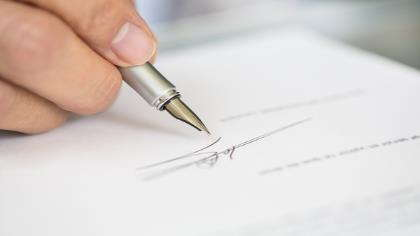 A hand signing an important document.