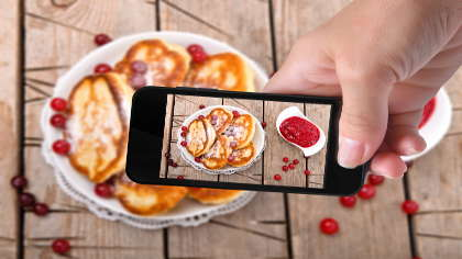A woman holding an iPhone and taking a photograph of a plate of pancakes.