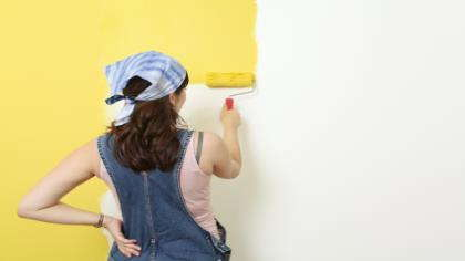 A woman paints a wall with yellow paint.