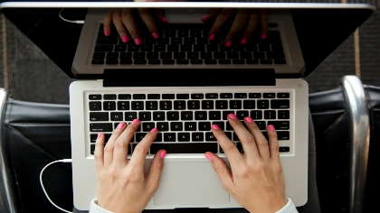 An overhead view of a pair of hands with pink fingernails typing on a keyboard.
