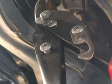 Tin snips make easy work of cutting the metal band holding the bellow on.