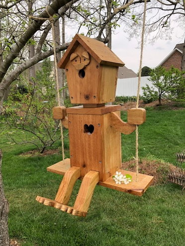 Woody the birdhouse is a-swinging from a branch on the pear tree.