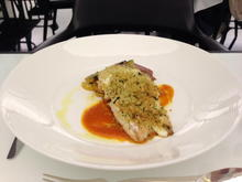 Baked sea bass with basil crust in roasted tomato coulis