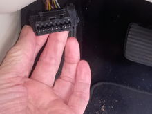 This is what the OBD11 port looks like, I believe it should be in the foot-well