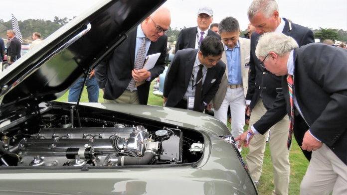 Judges at Pebble Beach examining a coachbuilt Jaguar | Bob Golfen photo
